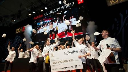 Alle Köche stehen gemeinsam auf der Bühne und werfen ihre Kochmützen hoch. Die Gewinner halten einen großen Scheck in den Händen.