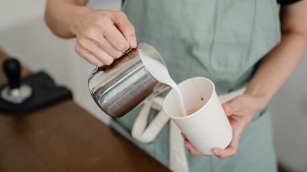 Barista füllt Kaffee in einen Becher aus Pappe