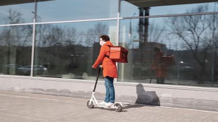 Mann liefert Essen auf E-Scooter aus