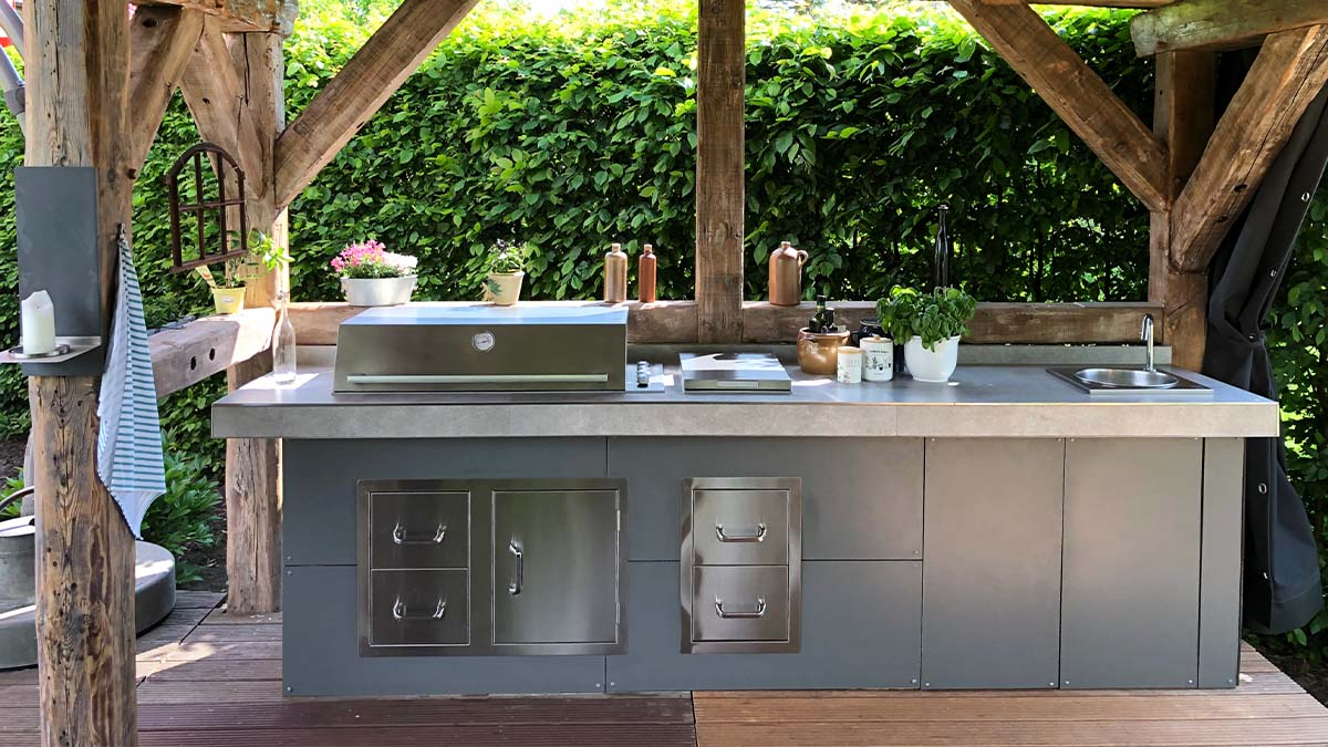 Outdoor kitchen with frame construction as a base with fronts in HPL, doors and drawers in stainless steel, Signature ProLine design grill and side burner all from BeefEater and built-in sink.