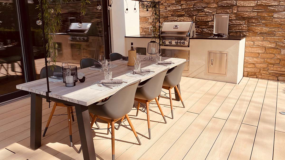 DIY outdoor kitchen with brick and plaster base, and dark natural stone countertop, with Napoleon BiPro 500 built-in grill with four burners and backburner, BeefEater ProLine side burner with 6kW and sink.