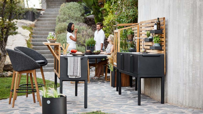 Outdoor kitchen with stainless steel work surface and cooking station