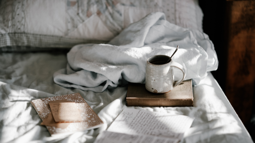 Bed with a cup, a book and a blanket